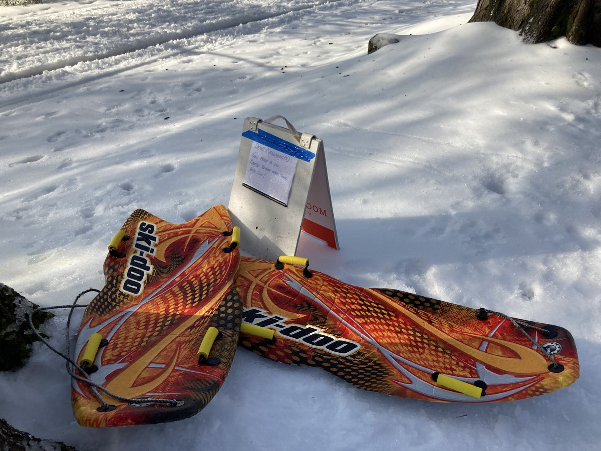 "Neighborhood ski/sleds. Sign reads ""Dear neighbor(s) Feel free to use. Please return when done. Have fun!"""